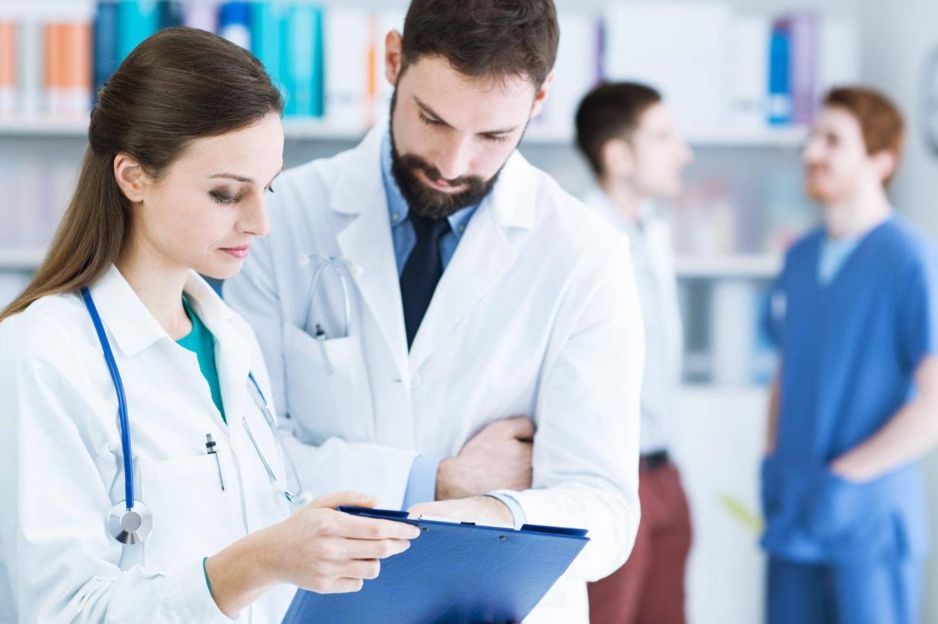 Femme médecin présentant un document à un homme médecin
